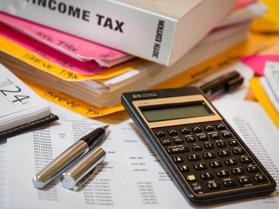 na stole kalkulator, długopis i książki o podatku