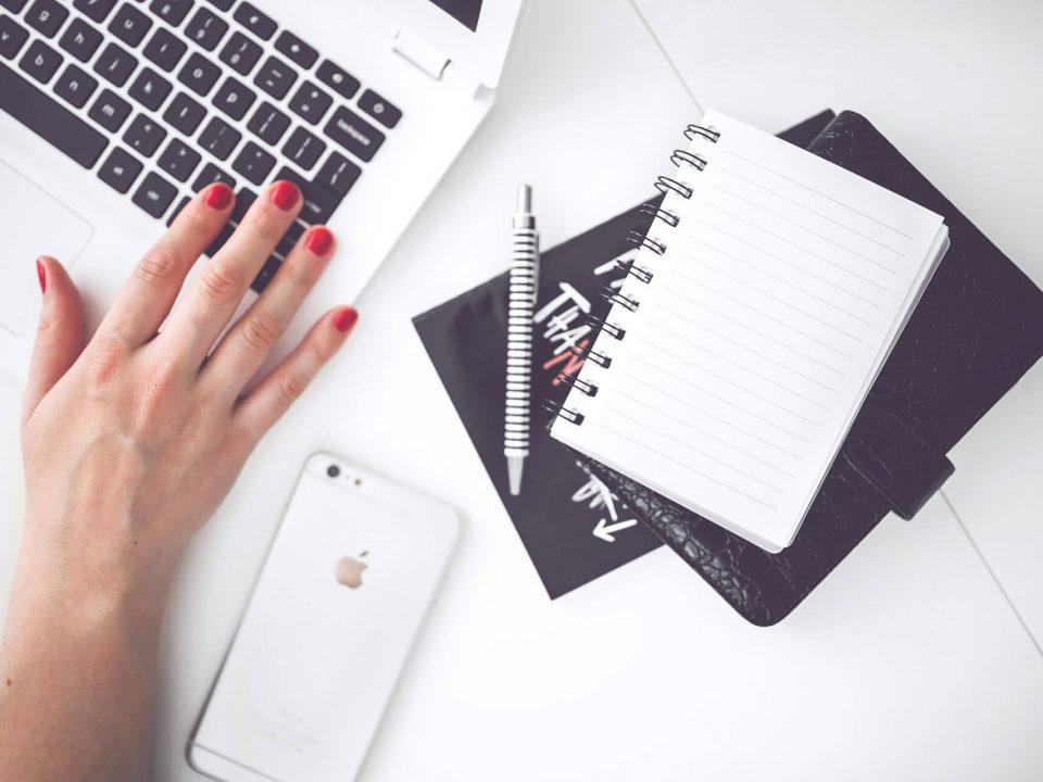 komputer, notatnik i damskie dłonie z czerwonym lakierem do paznokci