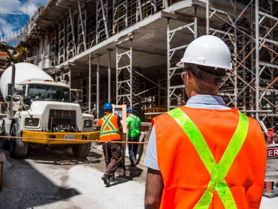 budowa w tle, na pierwszym planie kierownik budowy w białym kasku i odblaskowej kamizelce