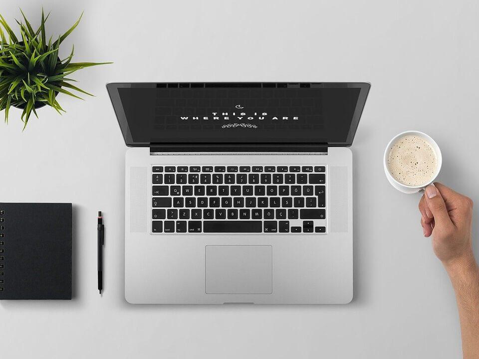 na biurku laptop,, kawa, notes i kwiatek zielony